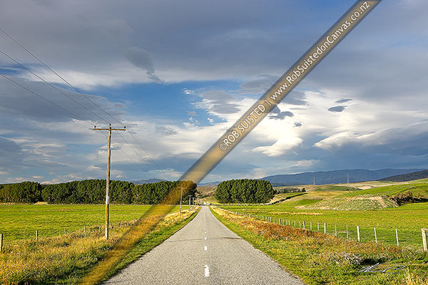 Photo of Rural country road, powerlines and farmland with moody cloudy sky above just before southerly storm front, Bendigo, Central Otago District, Otago Region, New Zealand (NZ)